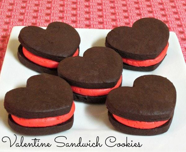 Valentine Sandwich Cookies- Creamy pink buttercream sandwiched between delicious homemade chocolate heart shaped cookies. A fancier and prettier version of homemade Oreos.