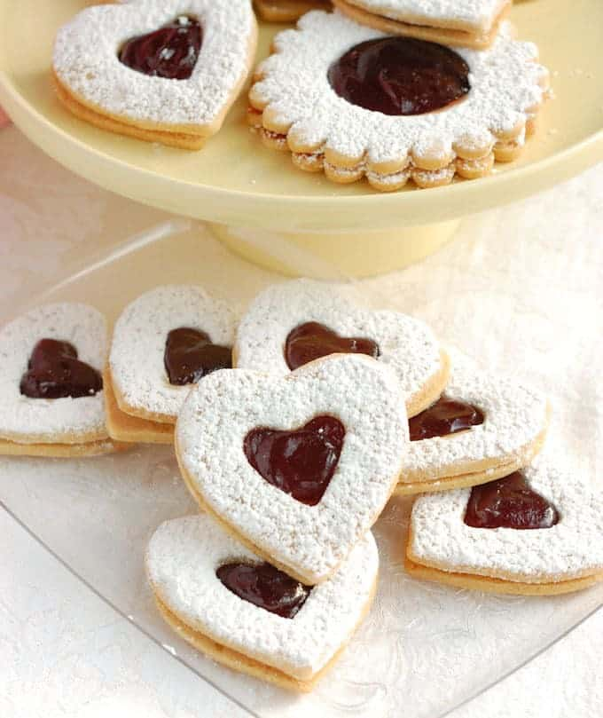 Raspberry Linzer Cookies are the perfect little cookie – Tender almond cookie dough sandwiched with raspberry preserves. Just a hint of rum gives the cookie a special flavor.