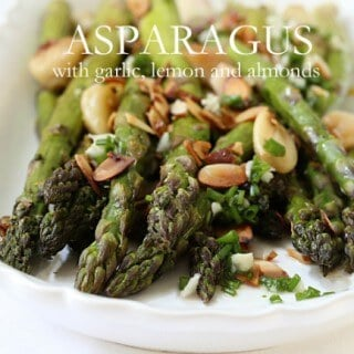 This Roasted Asparagus with Lemon and Garlic is the perfect side dish if you're grilling steak, chicken or pork on the BBQ! The garlic in this dish comes two ways – roasted and minced, which is mellowed by the added lemon and toasted almonds. | Featured on The Best Blog Recipes