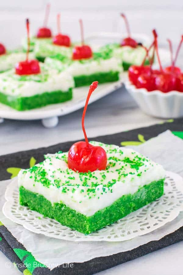 These soft mint Shamrock Shake Sugar Cookie Bars are a fun and easy treat. White frosting, green sugar, and a cherry make them look like the popular shake.