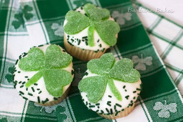 Luscious lemon cupcakes topped with lemon cream cheese frosting, sprinkles and a cute gumdrop shamrock.