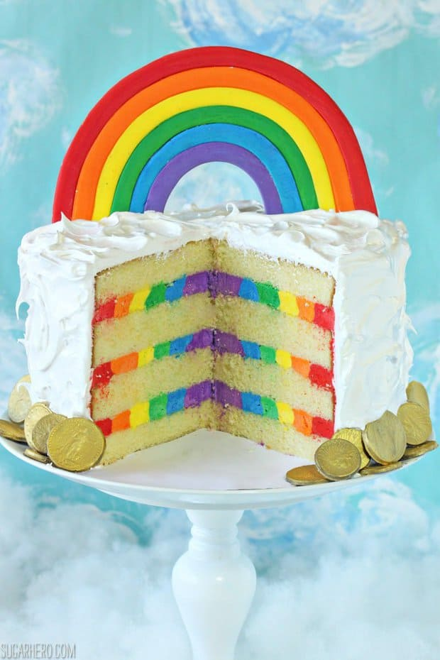 This gorgeous Rainbow Cake features moist yellow cake, striped rainbow frosting inside, and a light and fluffy cloud-like meringue on the outside! Make it for St. Patrick's Day, or any fun party!