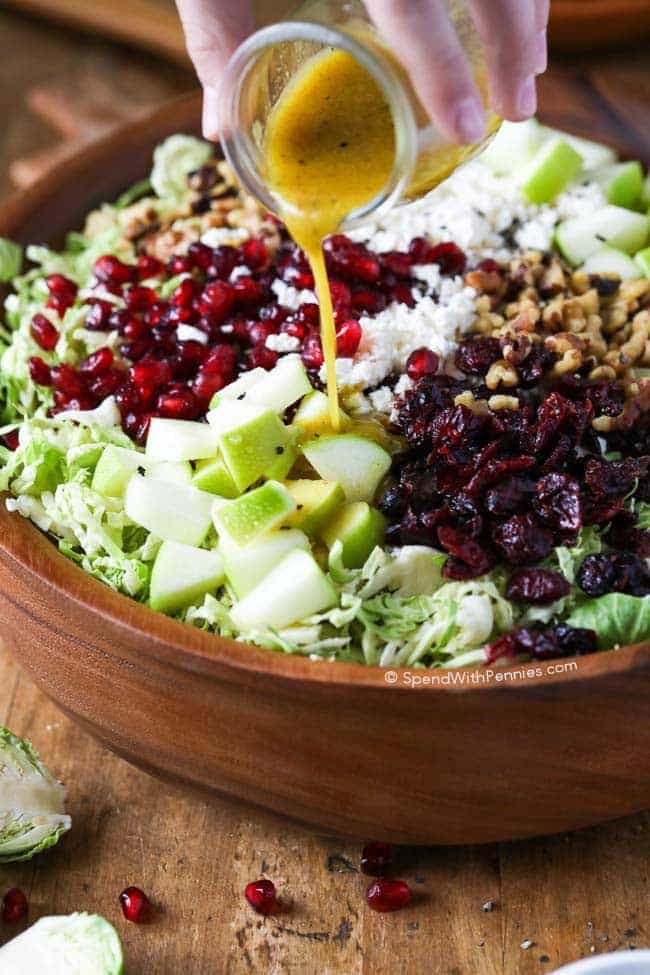Brussels Sprout Salad. Shredded Brussels sprouts, crisp tart apples, feta cheese, cranberries, pomegranate arils and walnuts all tossed in a tangy honey dijon vinaigrette.  This makes a perfect side or lunch.