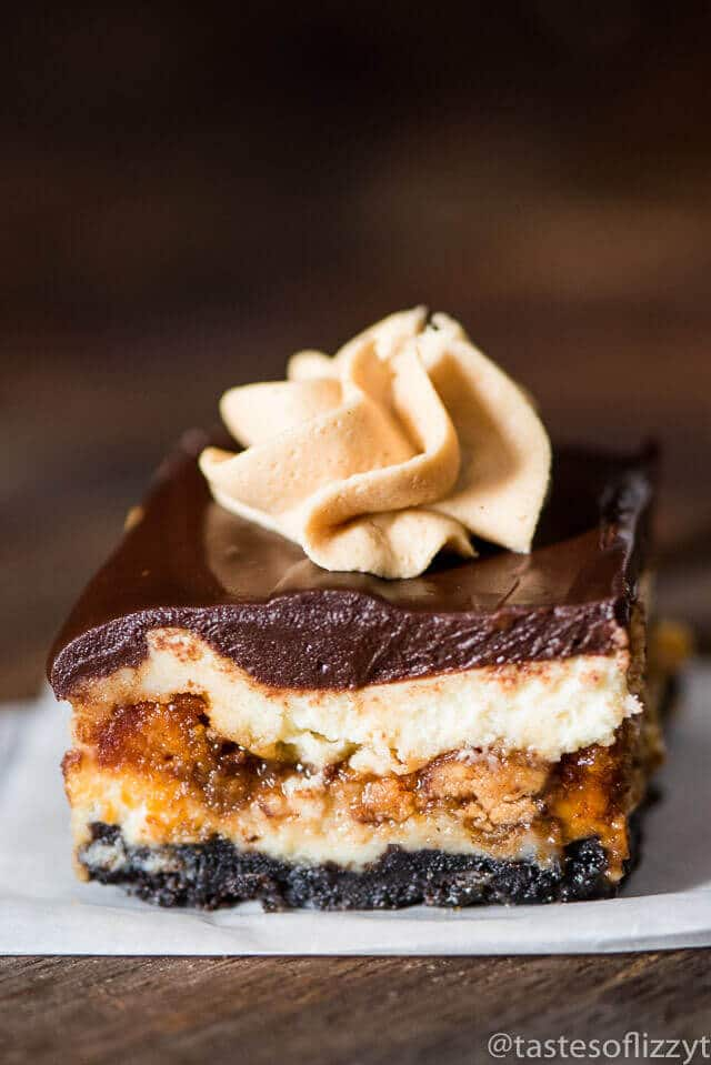 Reese's Butterfinger Cheesecake Bars are our copycat version of The Cheesecake Factory's Adam's Peanut Butter Cup Fudge Ripple Cheesecake. Creamy cheesecake stuffed with two kinds of candy bars, caramel, and topped with chocolate ganache and peanut butter frosting