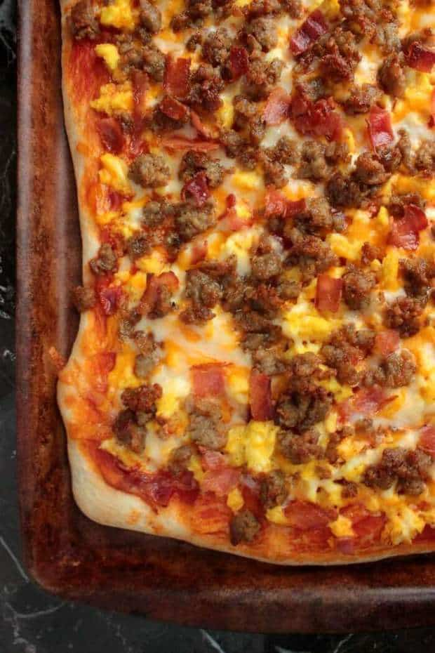 This breakfast pizza has scrambled eggs, sausage, bacon and cheese on it. It's everything you love about breakfast in pizza form and perfect for Saturday morning breakfast.