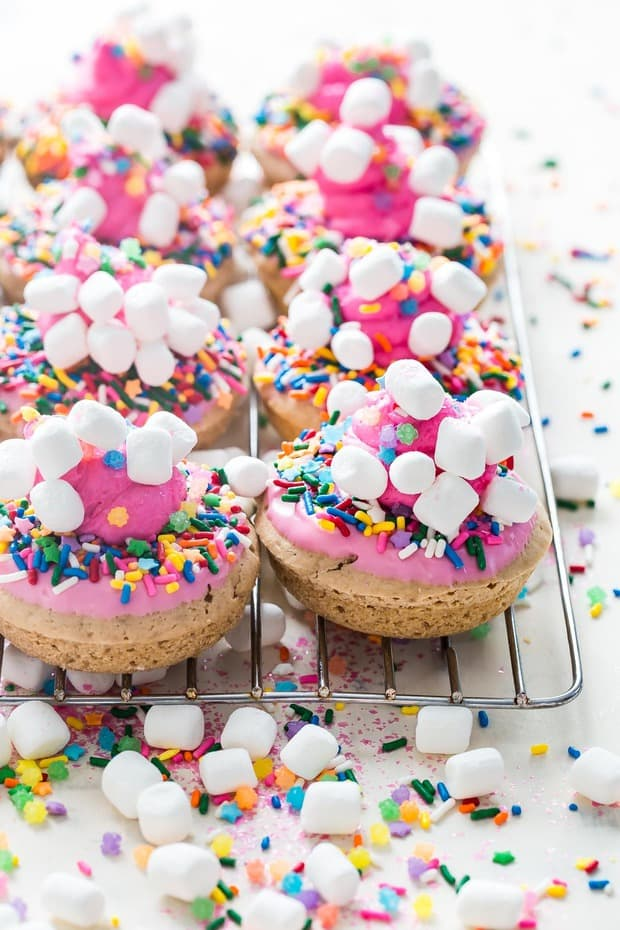 Baked strawberry donuts covered in an absurd amount of unicorn sprinkles and mini marshmallows! These color explosions are guaranteed to put a smile on your face.