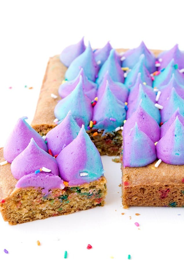 Buttery funfetti cookie squares filled with white chocolate chips and topped with purple and turquoise buttercream.