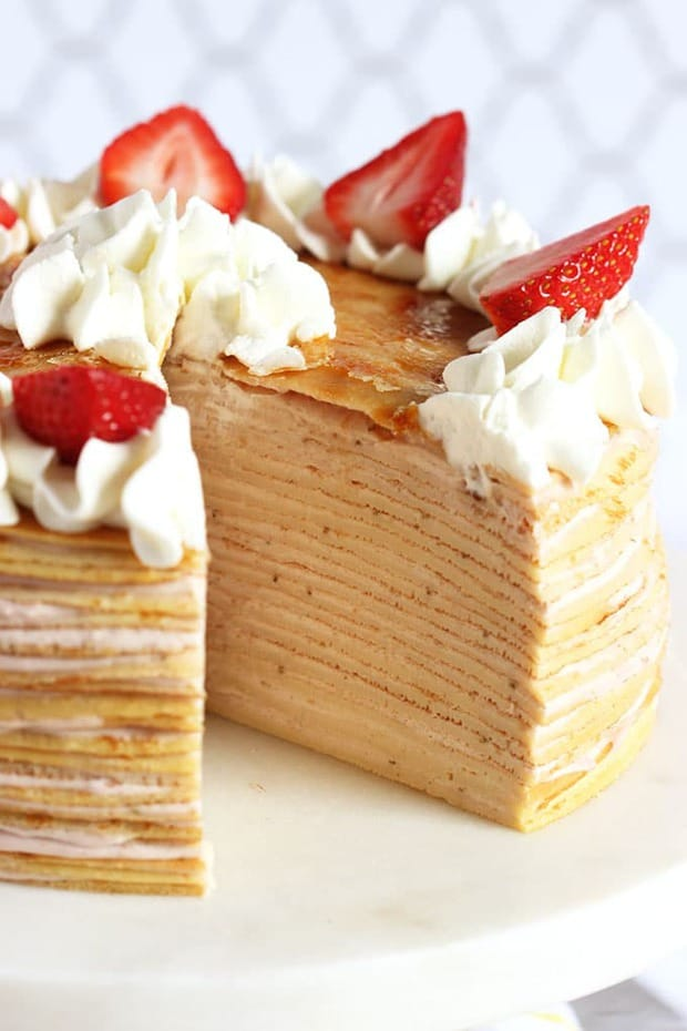 Light, delicate crepes are layered with a simply strawberry-mascarpone cream to create the easiest and most perfect spring cake. This Strawberry Cream Crepe Cake will be a favorite for the warmer months ahead. And no baking required.