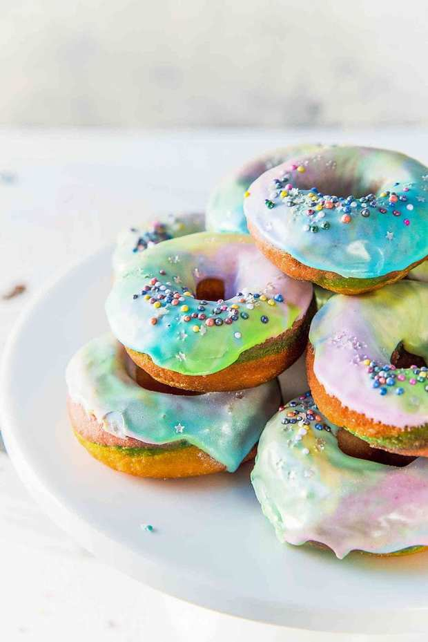 Soft, perfectly sweet with a hint of citrus flavor, these Mini Unicorn Rainbow Donuts are colorful and gorgeous inside and out, with a swirled rainbow colored dough and a colorful, rippled unicorn glaze, complete with stars and glitter. Perfect for fun kids' parties, themed parties, entertaining, or to celebrate all the unicorns in your life!