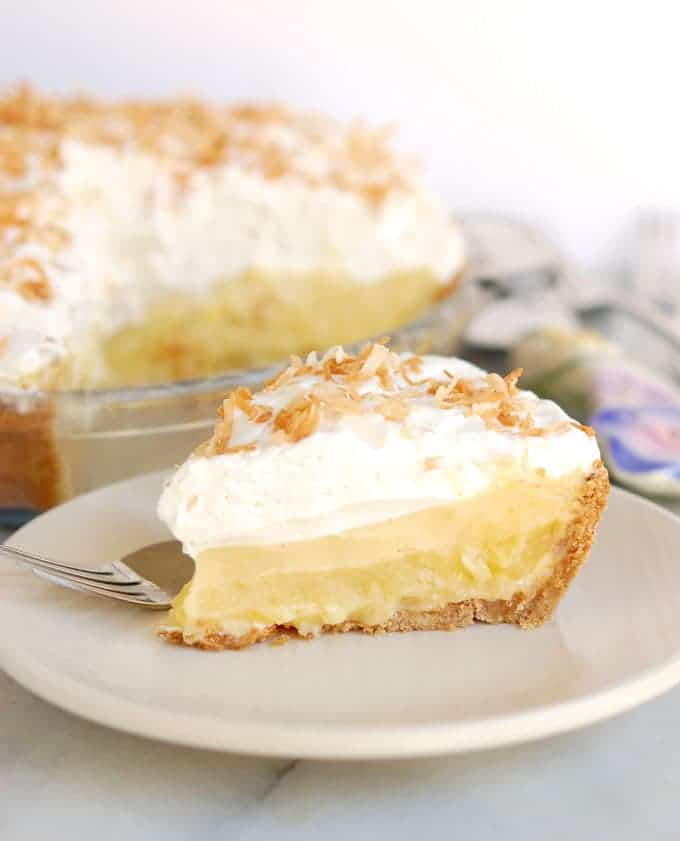 If you like Piña Coladas…..You'll love Piña Colada Pie!!! A toasted coconut-graham cracker crust is filled with a layer of pineapple/rum curd, a layer of coconut/rum cream and topped with a mound of rum-spiked whipped cream and, finally, a sprinkle of toasted coconut.