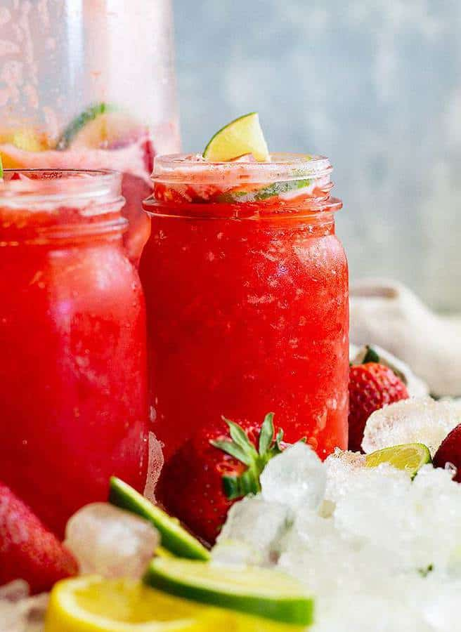 Strawberry Lemonade Margarita is an easy and crowd pleasing drink! It's ready in minutes when you use frozen lemonade even frozen strawberries if you desire. Make this Lemonade Margarita for your summertime parties!