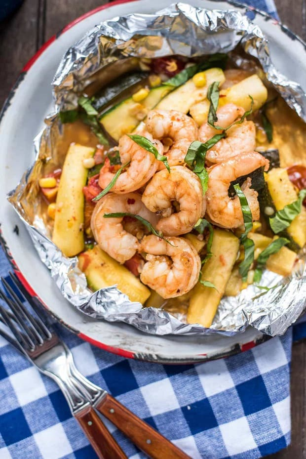 Honey Garlic Shrimp Foil Packets are packed with the best summer has to offer–zucchini, corn, tomatoes, and fresh basil in a sweet and sticky glaze.