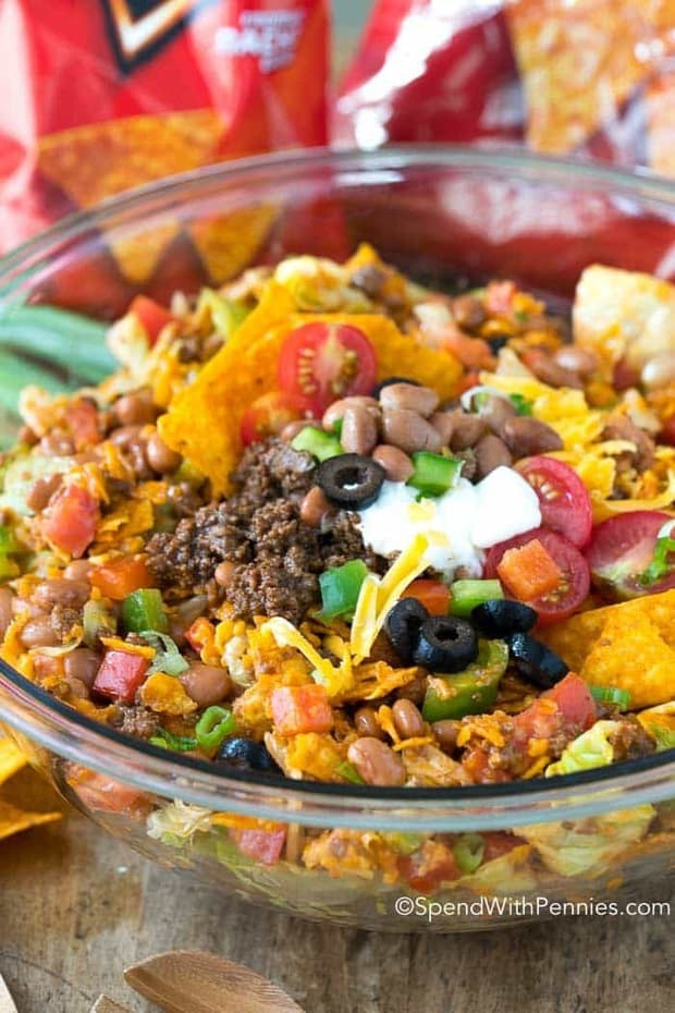 Dorito Taco Salad is a delicious salad we've been serving at potlucks for as long as I can remember! Seasoned ground beef, fresh lettuce, pinto beans, veggies and of course Doritos all sauced up with a zingy dressing make this an exciting change to your daily menu!
