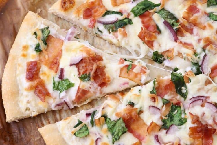 Bacon Alfredo Pizza baked fresh and full of flavor! Easy pizza recipe made with Alfredo sauce, bacon, red onion, spinach and lots of mozzarella cheese