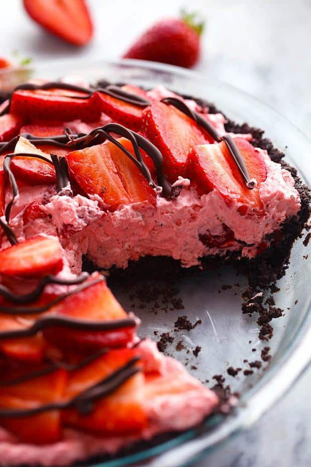 An amazing no bake pie with a chocolate crust filled with a creamy strawberry filling.  It gets topped with fresh strawberries and drizzled in chocolate and will be a huge hit wherever it goes!