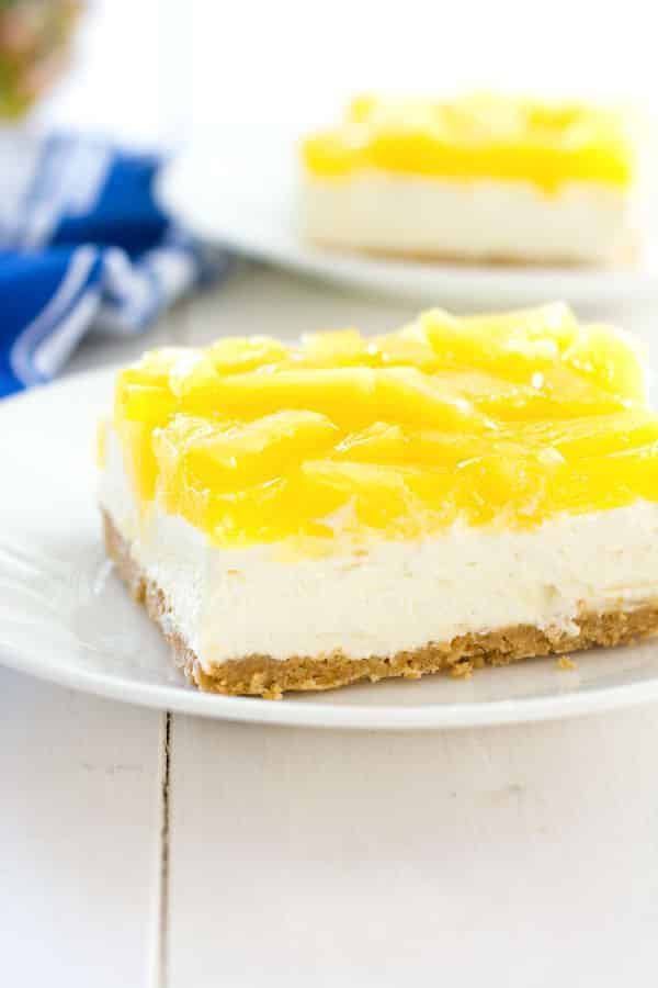 No-bake pineapple cheesecake bars taste like cool tropical sunshine! There are three layers of delicious starting with a graham cracker crust, thick cream cheese filling and crowned with a juicy pineapple topping.