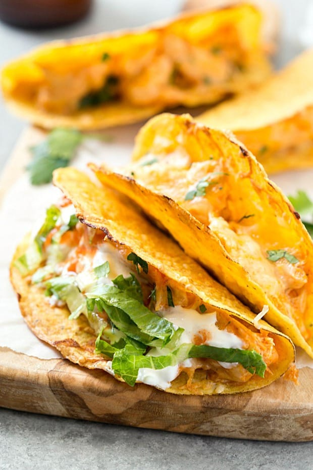 Oven Baked Buffalo Chicken Tacos – These super easy oven baked tacos are loaded with creamy buffalo chicken mixture and then topped with extra shredded cheese! Perfect recipe for taco Tuesday or any day of the week! So much flavor without all of the mess.