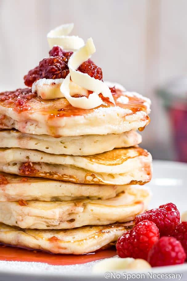 Fluffy pancakes packed with macadamia nuts, drizzled with a homemade raspberry maple syrup and garnished with shaved white chocolate. These Macadamia Nut Pancakes are what Sunday brunch is all about!