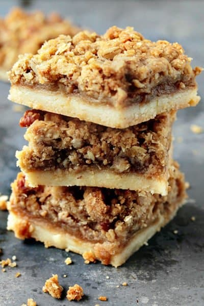 Apple Pie Bars start with a rich, buttery shortbread crust that is topped with a layer of tart apples that are beautifully accentuated by a perfect blend of autumnal spices. To make these already incredible bars even better, a layer of sweet and nutty crumble adds just the right amount of crunch. These Apple Pie Bars are seriously so good!!
