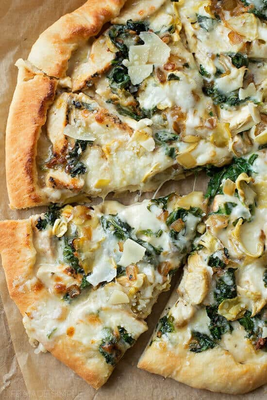 My favorite homemade pizza crust topped with a creamy garlic white sauce, mozzarella, chicken, spinach, and artichokes. This spinach artichoke pizza tastes just like the dip,only better!