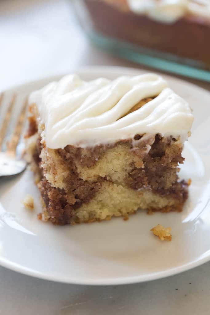Light and tender cinnamon roll cake with cream cheese frosting. All of the flavors I love from a cinnamon roll, in a delicious, easy cake recipe.