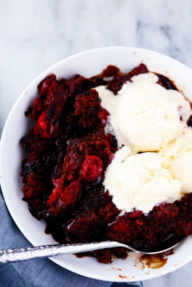 Slow Cooker Cherry Chocolate Hot Fudge Cake is a perfectly tender chocolate cake with hidden cherries inside.  It creates a magical fudge sauce while it is in the slow cooker and is completely irresistible!