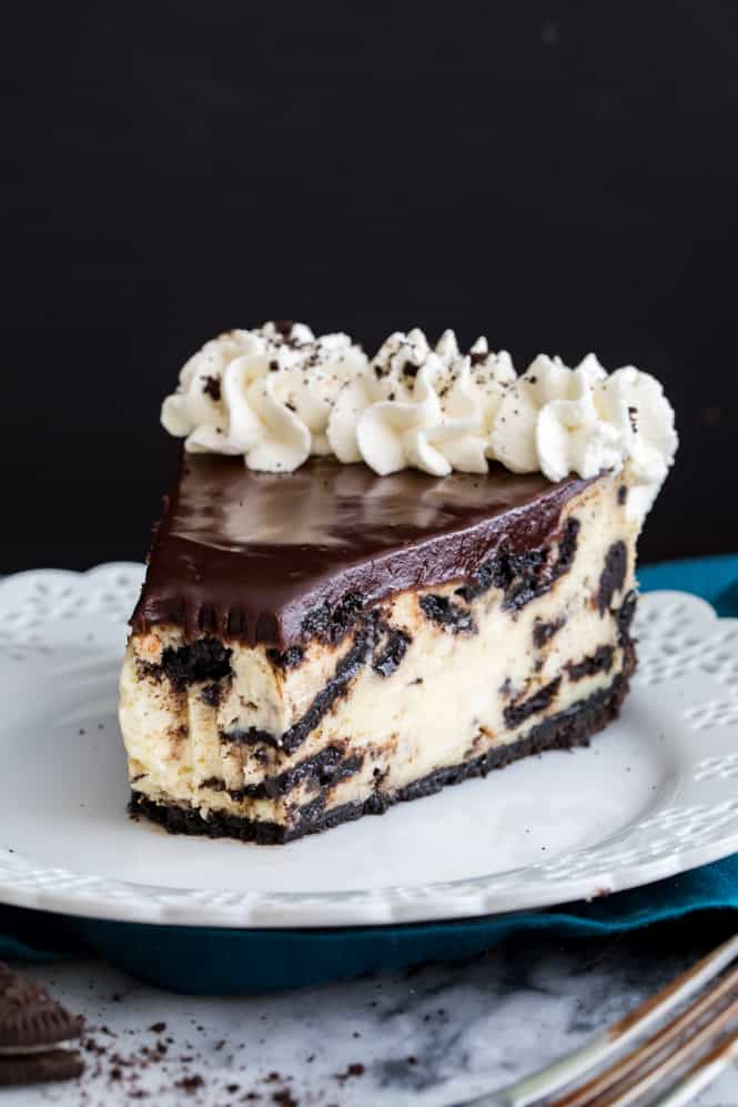 A creamy, cookies & cream filled Oreo Cheesecake! Served on an easy Oreo crust recipe and topped off with chocolate ganache and my homemade whipped cream, this cheesecake is not only a looker, it's also so easy to make and is utterly irresistible!
