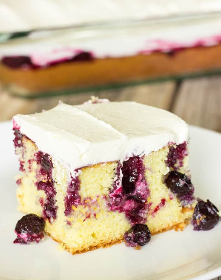 This blueberry lemon poke cake is to die for!  It's a lemon cake with holes poked in it.  Lemon blueberry sauce is drizzled on top of the cake so that the sauce and blueberries get down into the holes.  Then, it's topped off with a frosting made of lemon curd and cool whip.  Amazing!