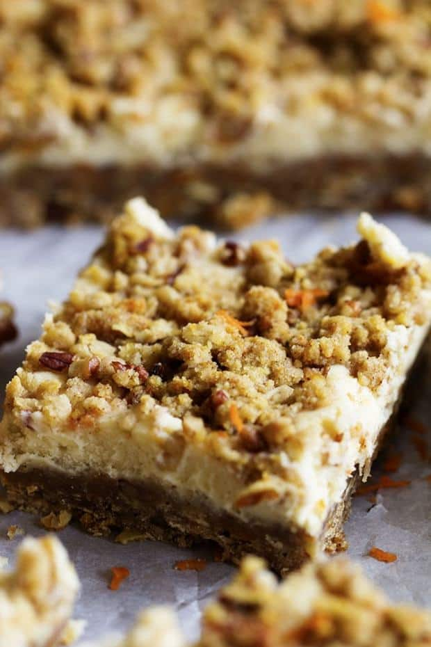 Crumbly spiced carrot cake bars with a delicious cheesecake center!  They are packed with flavor and sure to be a hit!