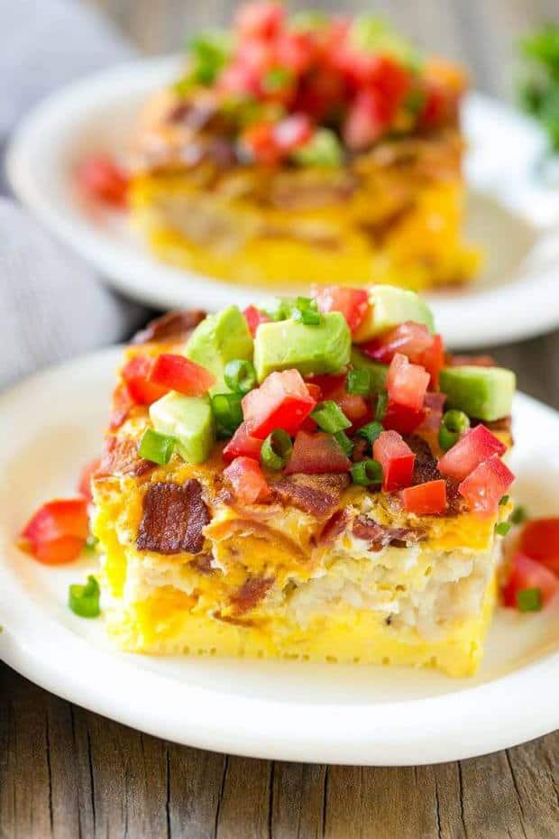 This breakfast casserole with bacon is loaded with eggs, bacon, potato tots and cheese, and is topped with tomatoes, avocado and herbs.