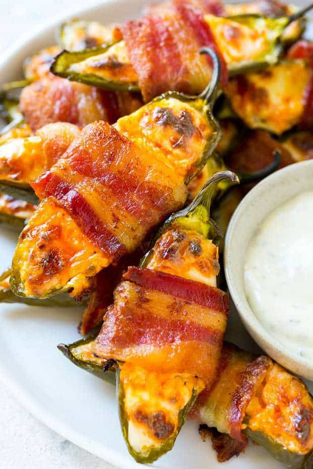These bacon wrapped jalapeno poppers are creamy, spicy and loaded with cheese. The perfect party appetizer!