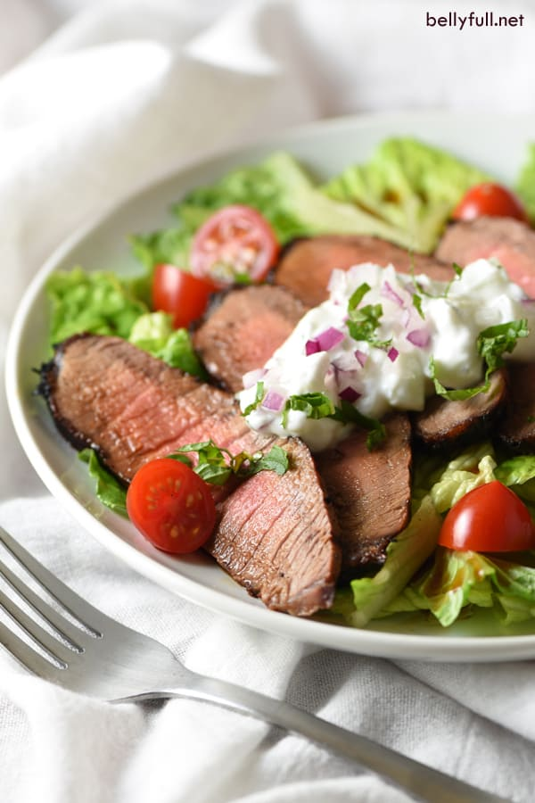 Grilled Steak Salad with Tzatziki Sauce – tender marinated steak is served on top of salad with a light and refreshing yogurt sauce for an easy, low-calorie meal!
