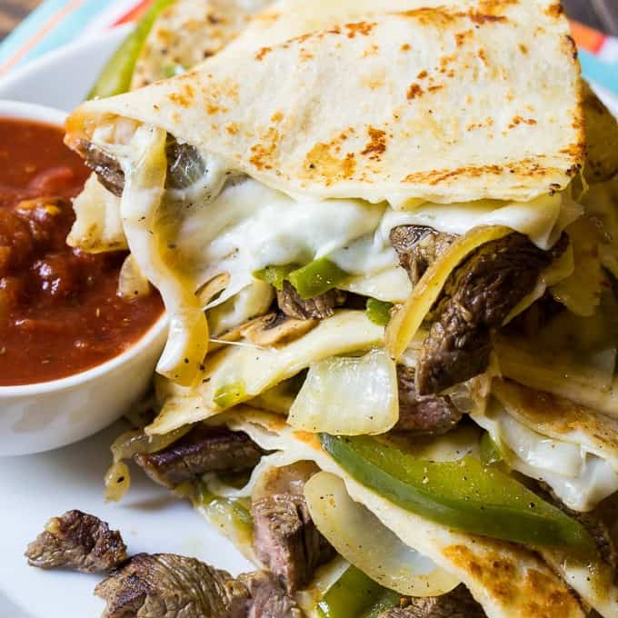 Philly Cheese Steak Quesadillas are filled with melted provolone cheese, tender crisp onions and peppers, fresh mushrooms, and seared steak slices. If you love a Philly Cheese Steak sandwich, you will love these quesadillas. They are perfect for game day!