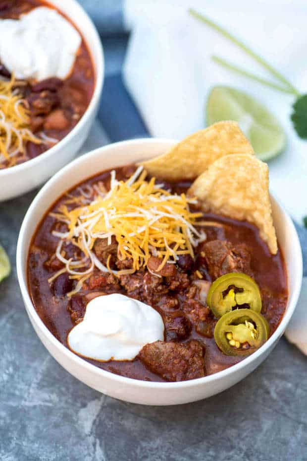ThisSlow Cooker Double Beef and Bean ChilifromValerie's Kitchenis hearty and has the most delicious blend of spices! Top with shredded cheese, sour cream, pickled jalapenos, and chips for dipping for the ultimate comfort meal!