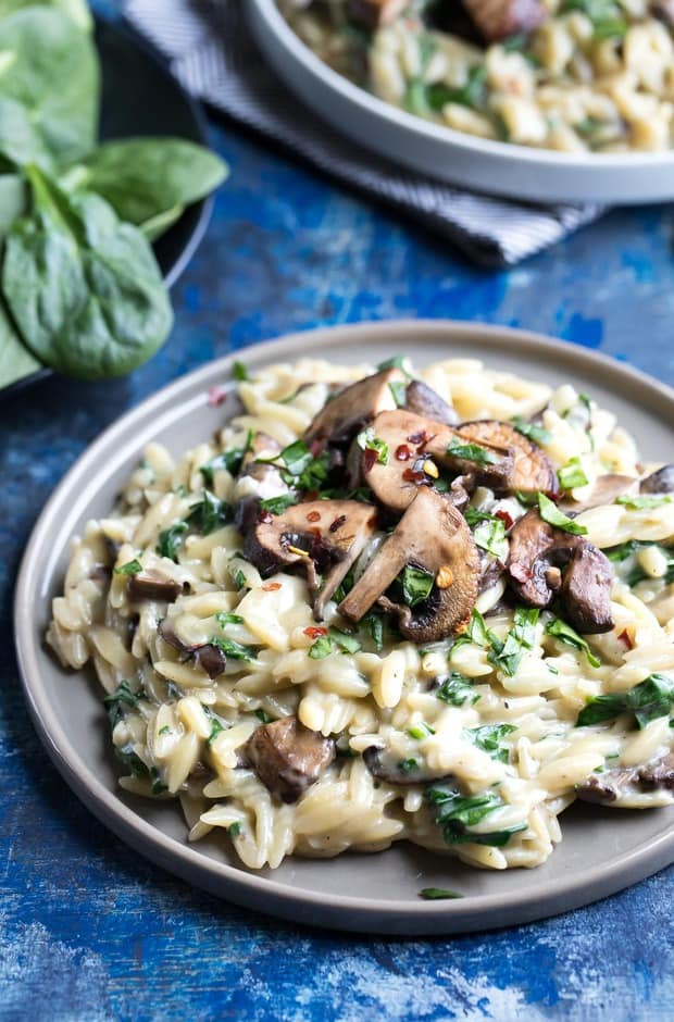 This One-Pot Garlic Parmesan Orzo with Spinach and Mushrooms is blanketed in a totally luscious sauce and swirled with veggies. This tasty vegetarian side dish also double as a main course!