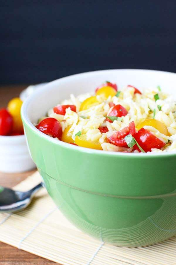 This Tomato Orzo Salad is a simple yet delicious summer salad with fresh tomatoes, orzo pasta and feta cheese tossed in a basil vinaigrette.