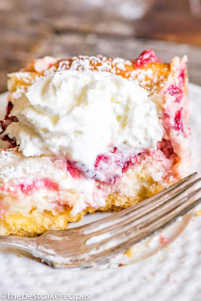 Ooey gooey butter cake never looked so good! This Strawberry Lemonade Gooey Butter Cake uses fresh strawberries and is a delicious summer dessert.