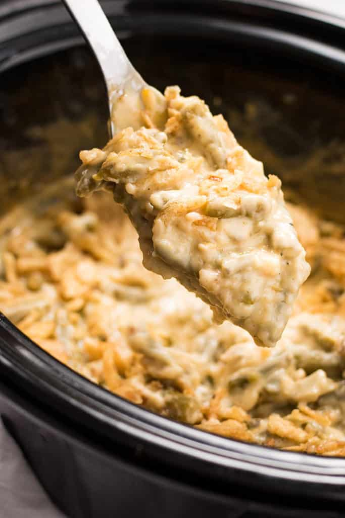 This Cheesy Crock Pot Green Bean Casserole recipe is everyone's favorite holiday side dish made even easier in the Crockpot!  Full of either fresh, frozen, or canned green beans, cream of mushroom soup, french fried onions and cheese this casserole is an easy crowd pleaser!
