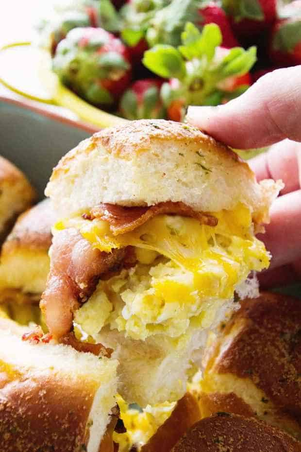 These delicious sliders are the perfect easy breakfast or brunch. An easy and delicious breakfast to feed a crowd, they are stuffed to the max with bacon, scrambled eggs, and gooey cheese.