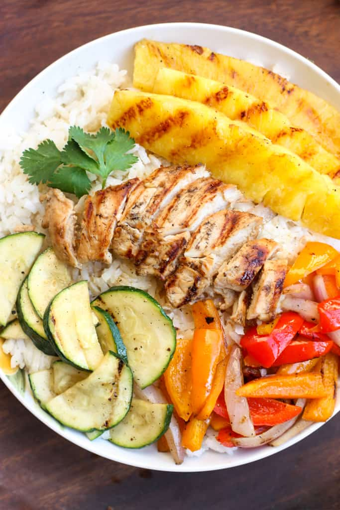 Grilled Hawaiian Chicken Teriyaki Bowls could be my all-time FAVORITE summer meal! The bowls start with a layer of coconut rice, topped with grilled pineapple, zucchini, bell peppers, and onions. Then, we add grilled teriyaki chicken and an extra drizzle of homemade teriyaki sauce over the top of everything. This amazing rice bowl is sure to be your new favorite dinner!