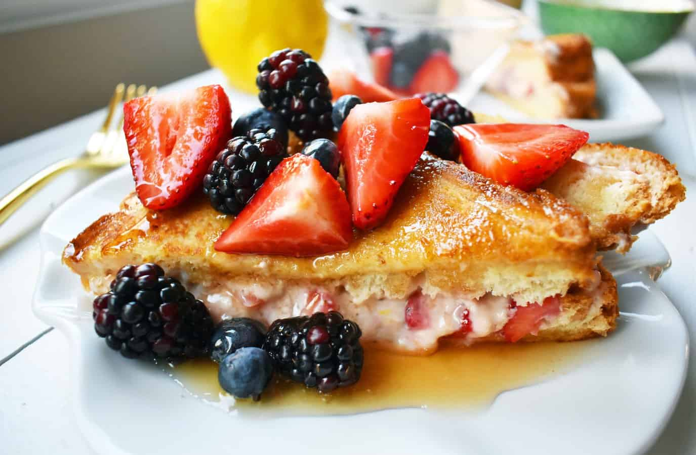A breakfast favorite! Sweetened fresh strawberry cream cheese stuffed between thick slices of bread and dipped into a rich custard batter and cooked in a buttery skillet until golden brown. Topped with fresh berries and homemade whipped cream. A showstopping breakfast dish!