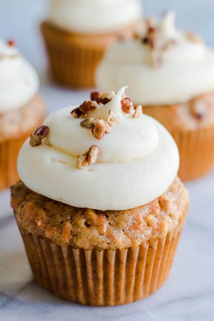 Carrot Cake Cupcakes from scratch! Made with fresh carrots, tons of spice, greek yogurt and topped with a luscious cream cheese frosting. These are the perfect cupcakes