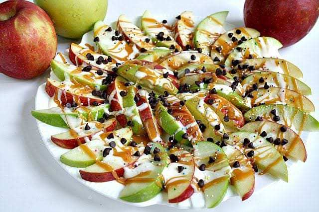 Caramel Apple Nachos are easily made by topping sliced apples with caramel, melted marshmallows, chocolate chips and sprinkles! She are perfect for an appetizer or for just a fun dessert. Perfect for both adults and kids! Everyone will love this recipe!