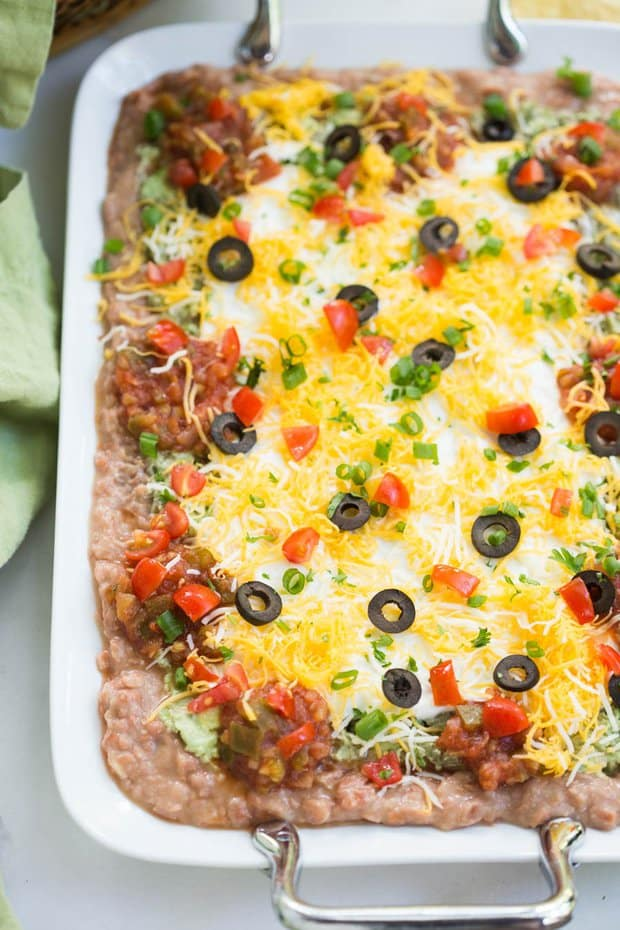 It's not a football party at our house without a big platter of 7-layer bean dip! Everyone loves this easy Mexican dip that has layers of flavored refried beans, guacamole, sour cream, salsa, cheese, olives and green onion.