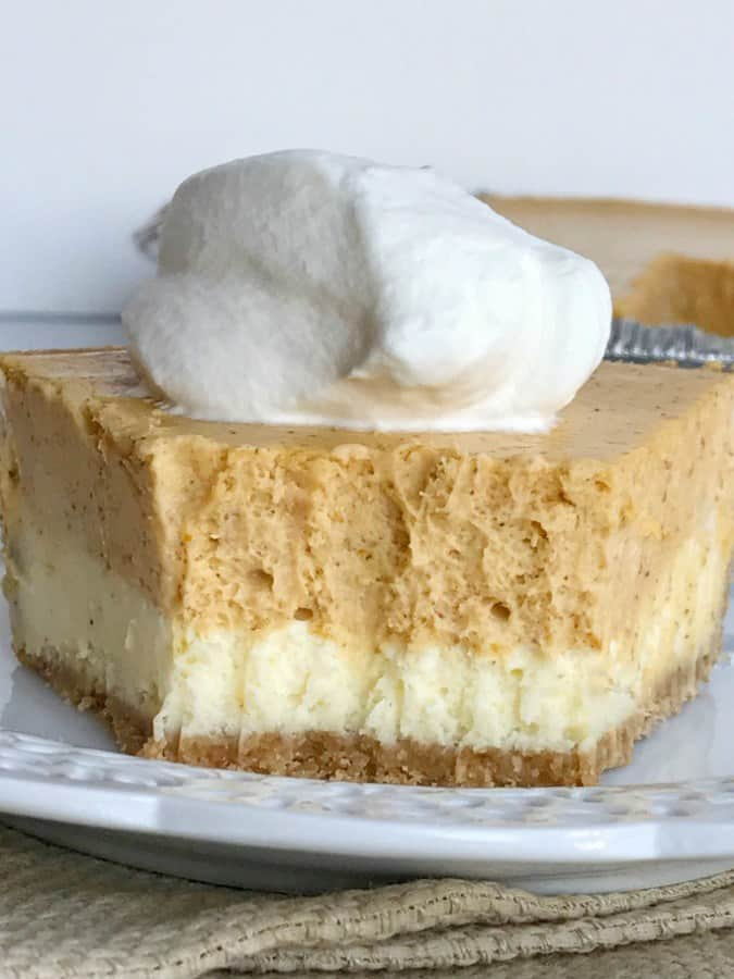 Double layer pumpkin cheesecake pie has two layers of pumpkin cheesecake inside a prepared graham cracker crust. This is an easy cheesecake recipe that even beginners can make. Top with some fresh whipped cream for the ultimate Fall dessert or add it to your Thanksgiving dessert table!