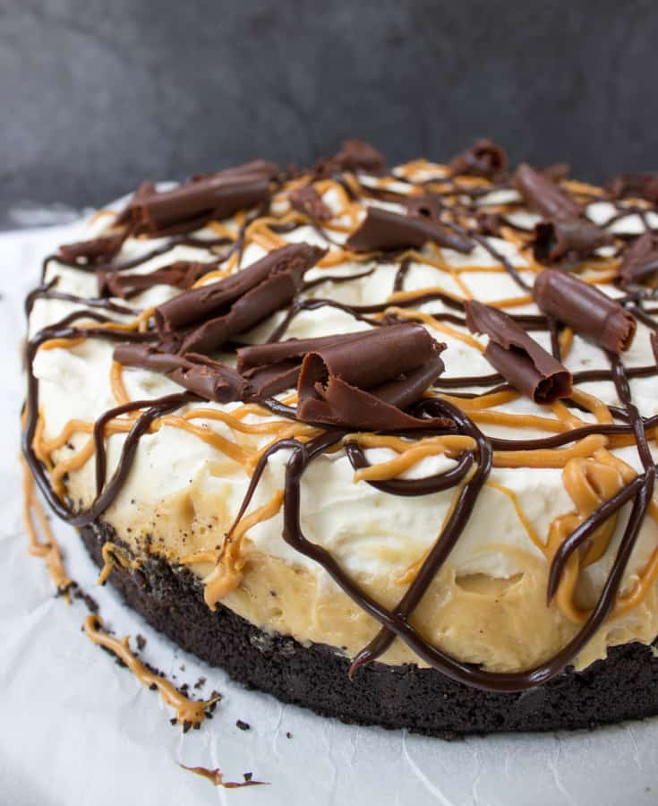 This deep dish peanut butter chocolate pie is made on an Oreo based crust covered by a thick chocolate ganache, layered with a scrumptious cream-cheese based peanut butter pie filling and topped with sweet, stabilized whipped cream, then drizzled with chocolate sauce, peanut butter sauce, and homemade chocolate curls.   A classic flavor combination that is delectable, but not cloying.  The crust is baked briefly in the oven to ensure sturdiness while the fillings are no-bake.