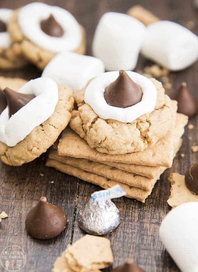 Peanut butter s'mores cookies have a peanut butter graham cracker filled cookie, topped with a gooey marshmallow, and a chocolate Hershey kiss. They combine the great taste of s'mores and peanut butter into a delicious cookie!