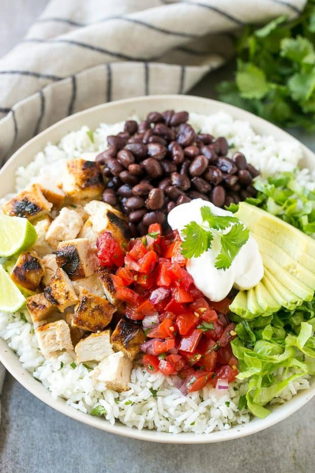 These Burrito Bowls are loaded with marinated grilled chicken, cilantro lime rice, black beans and a variety of fun toppings. This recipe will become a dinnertime sstaple at your house!