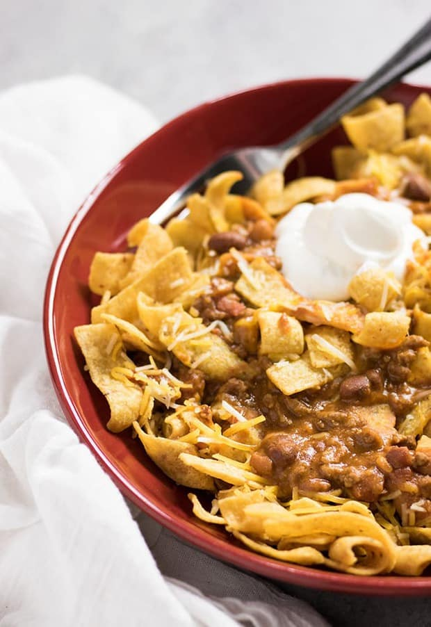 Crockpot Frito Chili Pie – A recipe for Frito pie made simple using your crockpot!  Simple homemade chili with plenty of cheddar cheese and crunchy Fritos corn chip topping.