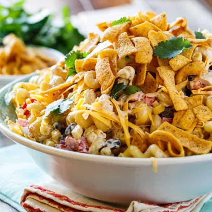 BBQ Ranch Pasta Salad is sure to become a picnic favorite this spring and summer. It's creamy and full of smoky flavor, sour cream, black beans, corn, red bell pepper, red onion, cilantro, diced chicken, shredded cheddar cheese, and the wonderful crunch of corn chips.